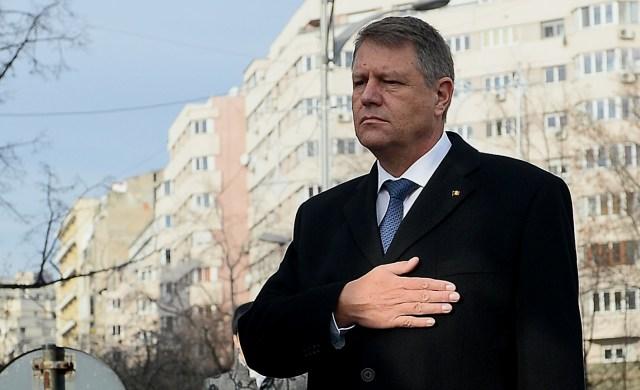 Klaus Iohannis, acoperind inima cu mana