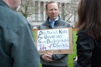 "Randy Holland, a pediatric surgeon at a Tacoma children's hospital hold's a sign while in line for the hearing on I-594 on Jan. 28. ""I've cared for several children that have been injured by guns and gun safety is to limit the injuries that can happen to children."" Holland says that most of the time, ""the accidents we see that are criminal are often drive by shootings. So the children unlucky to be in harm's way. Thankfully, [it's] fairly rare that it's intentional to injure a child with a firearm."""