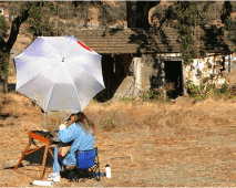 """Nixon painting in """"plein"""" air at the lost mission, (Mission #23), the St. Eulalia Mission, (ca. 1834) that she discovered by accident while searching for a place to paint. This last mission was built after the Sonoma Mission as an """"Assistencia"""" to the Sonoma Mission by Father Jose Altimira, and managed by Native American neophyte, Chief Solano, who grew up in the Sonoma Mission as a boy after his tribe was slaughtered by missionaries in Cordelia. The St. Eulalia Mission was """"lost"""" for many years because pioneers built a winery and barns around it. The records of St. Eulalia were kept at the Dolores Mission in San Francisco so historians knew it existed but not sure where the remains were. After the old barns surrounding it were torn down at the Mangels Winery in the Rockville-Cordelia area, Nixon discovered it, surrounded by bulldozers poised to destroy it, and asked her historian friend why this adobe was there, underneath an old barn for so long. This lead to the last mission's discovery, and started a new historical debate about which town has the last California Mission...Sonoma or Cordelia? This just goes to show that you never know what you may find when you go out plein air painting!"""