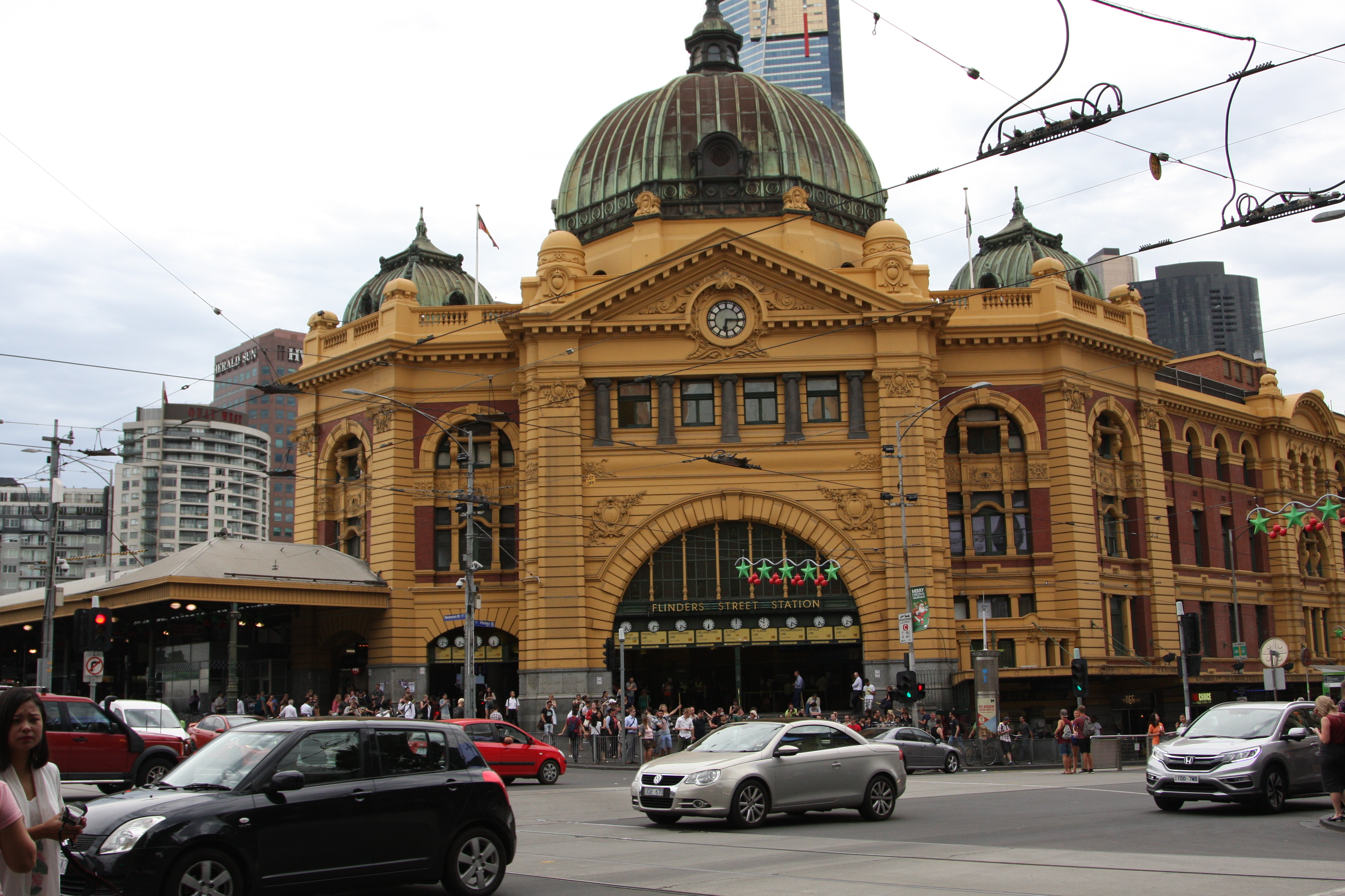 in front of the Flinders Street Train Station with cars and a few Christmas decorations
