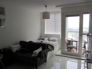 the bed, couch, and kitchen in one room with windowed door to the balcony in the Airbnb in Amsterdam