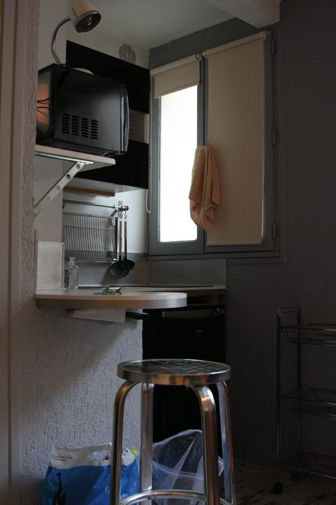 microwave, dishwasher,window, and counter stool in the little kitchenette in the Airbnb rental in Paris