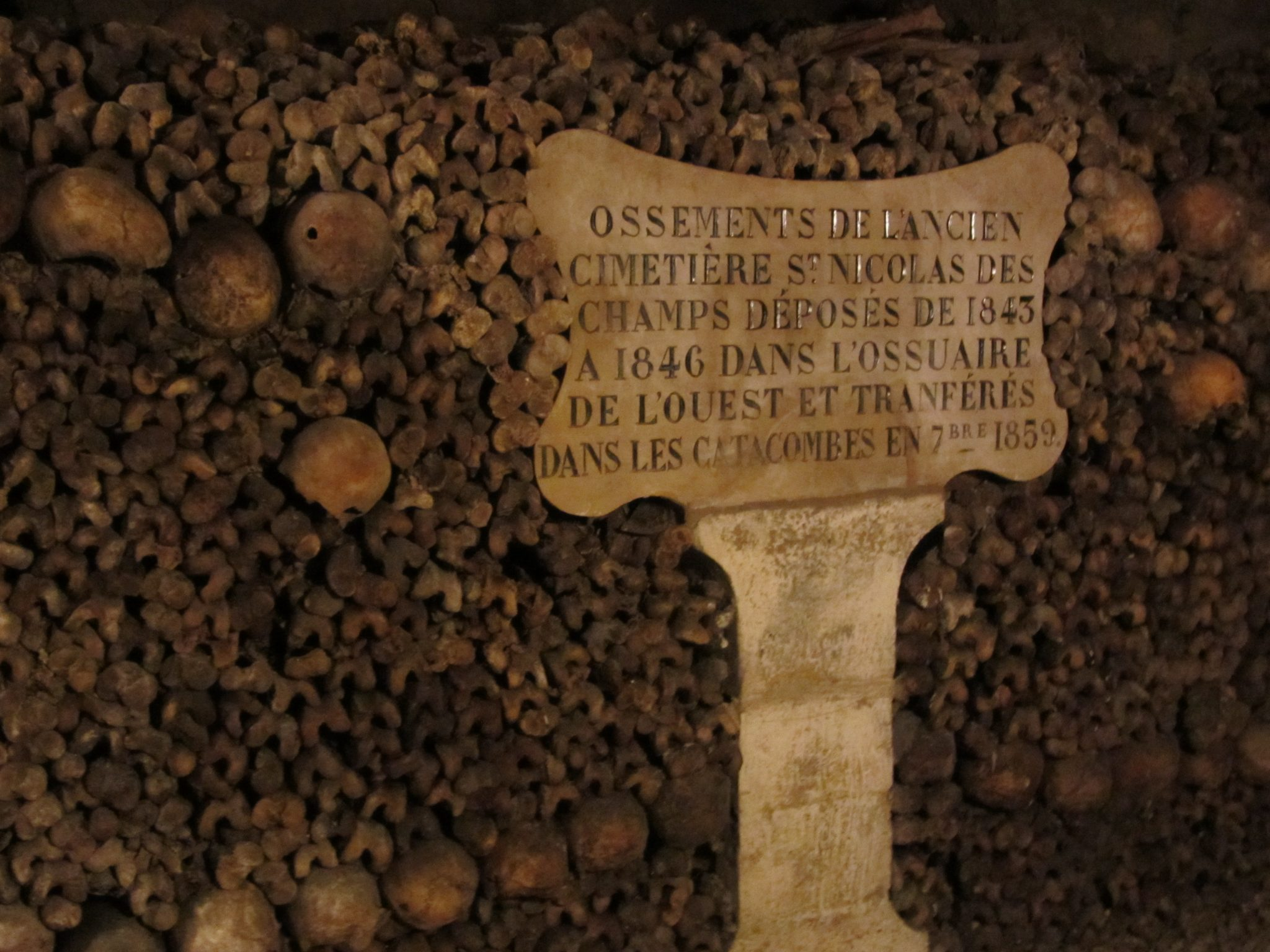 Sign in French Amongst the Bones in the Catacombs of Paris