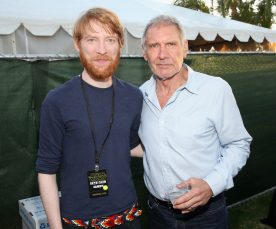 SAN DIEGO, CA - JULY 10: Actors Domhnall Gleeson (L), Harrison Ford and more than 6000 fans enjoyed a surprise `Star Wars` Fan Concert performed by the San Diego Symphony, featuring the classic `Star Wars` music of composer John Williams, at the Embarcadero Marina Park South on July 10, 2015 in San Diego, California. (Photo by Jesse Grant/Getty Images for Disney) *** Local Caption *** Domhnall Gleeson; Harrison Ford
