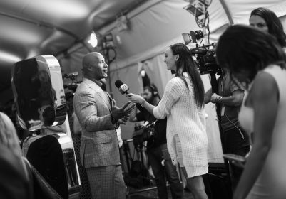 """HOLLYWOOD, CA - NOVEMBER 14: (EDITORS NOTE: Image has been shot in black and white. Color version not available.) Actor Dwayne Johnson (L) is interviewed at The World Premiere of Disney's """"MOANA"""" at the El Capitan Theatre on Monday, November 14, 2016 in Hollywood, CA. (Photo by Charley Gallay/Getty Images for Disney) *** Local Caption *** Dwayne Johnson"""