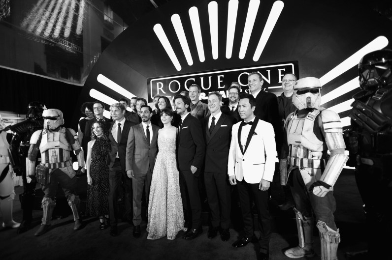 """HOLLYWOOD, CA - DECEMBER 10: (EDITORS NOTE: Image has been shot in black and white. Color version not available.) (L-R front row) Producer Allison Shearmur, actors Mads Mikkelsen, Riz Ahmed, Felicity Jones, Diego Luna, Alan Tudyk and Donnie Yen (back row) Director Gareth Edwards, Producer Kathleen Kennedy, actor Ben Mendelsohn, composer Michael Giacchino and The Walt Disney Company Chairman and CEO Bob Iger attend The World Premiere of Lucasfilm's highly anticipated, first-ever, standalone Star Wars adventure, """"Rogue One: A Star Wars Story"""" at the Pantages Theatre on December 10, 2016 in Hollywood, California. (Photo by Charley Gallay/Getty Images for Disney) *** Local Caption *** Allison Shearmur; Mads Mikkelsen; Riz Ahmed; Felicity Jones; Diego Luna; Alan Tudyk; Donnie Yen; Gareth Edwards; Kathleen Kennedy; Ben Mendelsohn; Michael Giacchino; Bob Iger"""