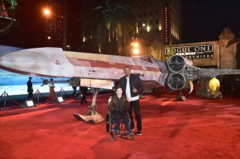 """HOLLYWOOD, CA - DECEMBER 10: Actor Micah Fowler (L) and guest attend The World Premiere of Lucasfilm's highly anticipated, first-ever, standalone Star Wars adventure, """"Rogue One: A Star Wars Story"""" at the Pantages Theatre on December 10, 2016 in Hollywood, California. (Photo by Marc Flores/Getty Images for Disney) *** Local Caption *** Micah Fowler"""