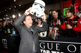 """HOLLYWOOD, CA - DECEMBER 10: Director Gareth Edwards puts on a fan's Stormtrooper helmet at The World Premiere of Lucasfilm's highly anticipated, first-ever, standalone Star Wars adventure, """"Rogue One: A Star Wars Story"""" at the Pantages Theatre on December 10, 2016 in Hollywood, California. (Photo by Jesse Grant/Getty Images for Disney) *** Local Caption *** Gareth Edwards"""