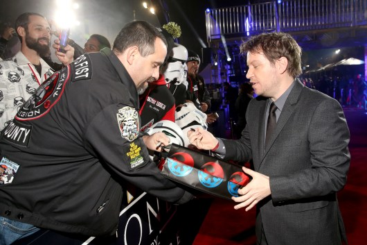 """HOLLYWOOD, CA - DECEMBER 10: Director Gareth Edwards signs an autograph for a fan at The World Premiere of Lucasfilm's highly anticipated, first-ever, standalone Star Wars adventure, """"Rogue One: A Star Wars Story"""" at the Pantages Theatre on December 10, 2016 in Hollywood, California. (Photo by Jesse Grant/Getty Images for Disney) *** Local Caption *** Gareth Edwards"""