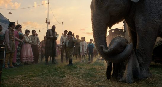 """CIRCUS FAMILY – In Disney's all-new live-action adventure """"Dumbo,"""" circus owner Max Medici (Danny DeVito) and circus performer Rongo the Strongo (Deobia Oparai)—plus the rest of their big-top team—welcome a newborn elephant with oversized ears to their tight-knit family. Directed by Tim Burton, """"Dumbo"""" flies into theaters on March 29, 2019. ©2018 Disney Enterprises, Inc. All Rights Reserved."""