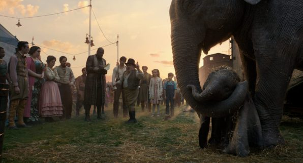"CIRCUS FAMILY – In Disney's all-new live-action adventure ""Dumbo,"" circus owner Max Medici (Danny DeVito) and circus performer Rongo the Strongo (Deobia Oparai)—plus the rest of their big-top team—welcome a newborn elephant with oversized ears to their tight-knit family. Directed by Tim Burton, ""Dumbo"" flies into theaters on March 29, 2019. ©2018 Disney Enterprises, Inc. All Rights Reserved."