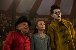 """CLOWNING AROUND -- In Tim Burton's all-new, live-action reimagining of """"Dumbo,"""" circus owner Max Medici (Danny DeVito) calls on former circus star Holt Farrier (Colin Farrell) to care for a newborn elephant whose oversized ears make him a laughingstock in an already struggling circus. Holt ultimately takes his task very seriously—even donning a clown suit to help the flying elephant as he emerges as a star. Daughter Milly (Nico Parker) just might be Dumbo's biggest fan. """"Dumbo"""" flies into theaters on March 29, 2019. Photo by Jay Maidment. © 2018 Disney Enterprises, Inc. All Rights Reserved."""