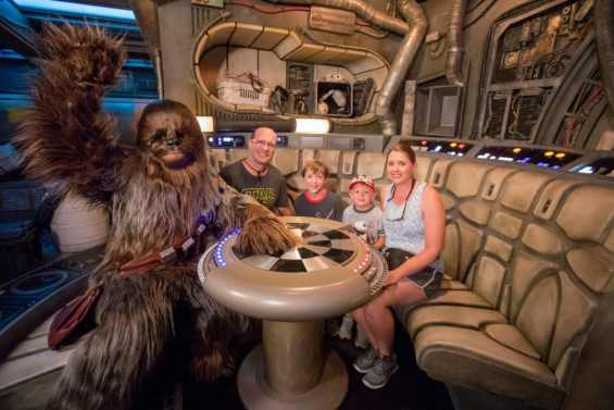 Eight-year-old Jonathan Ridgeway of Ocean Springs, Mississippi (center, back) becomes the 1 millionth guest to take to take the controls of Millennium Falcon: Smugglers Run at Star Wars: Galaxy's Edge at Disneyland Resort in Anaheim, Calif., Tuesday, July 16, 2019. Chewbacca joined (l-r) Rodger Ridgeway, Jonathan Ridgeway, 8, Logan Ridgeway, 4, and Becky Ridgeway for a photo. The family was welcomed in the Main Hold of Millennium Falcon with a surprise declaration, which included a visit by Chewbacca, followed by the ride experience and toasting blue and green milk with his family. This significant milestone comes just weeks since the land opened. (Joshua Sudock/Disneyland Resort)