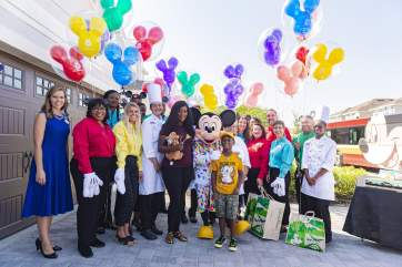 Mickey Mouse and Walt Disney World cast members pose with seven-year-old Jermaine Bell and his mother, Lauren Creech, during Jermaine's birthday party Sept. 8, 2019, in Kissimmee, Fla. Mickey and pals made a surprise appearance at the party to honor Jermaine who used money he'd saved for a Walt Disney World vacation to feed people fleeing Hurricane Dorian. Adding to a day filled with surprises, Jermaine learned that he and his family will be guests of Disney for a VIP getaway to the vacation kingdom later this month. (Disney)