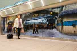 A traveler at Orlando International Airpott in Orlando, Fla., passes by a scene from Star Wars: Galaxy's Edge at Disney's Hollywood Studios prior to boarding a shuttle to the Main Terminal, Nov. 16, 2019. Disney installed these artistic wraps on the shuttle stations to immerse airport travelers in scenes from Star Wars: Galaxy's Edge. (Steven Diaz, photographer)