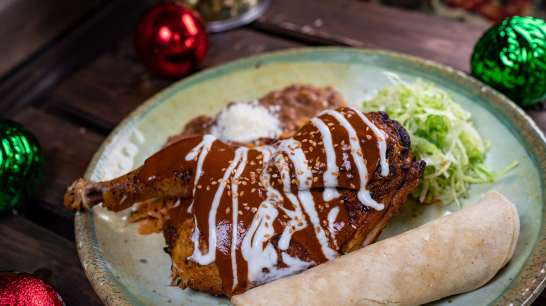 Chicken Mole is part of the limited-time holiday foods at The Disneyland Resort. Available November 8 - January 6, this dish is a seasoned half chicken topped with sour cream and sprinkled with toasted sesame seeds, served with Mexican rice and refried beans. This dish can be be purchased at Rancho Del Zocalo in Disneyland Park. (Disneyland Resort)