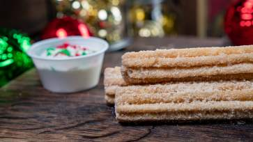 The Santa's Cookies and Milk Churro is part of the limited-time holiday treats at The Disneyland Resort. Available November 8 - January 6, this artisan churro is rolled in cookie butter sugar and served with a condensed milk dipping sauce. This treat can be be purchased at the Casey Jr. Churro Cart in Disneyland Park. (Disneyland Resort)