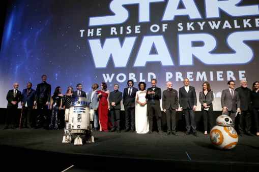 "HOLLYWOOD, CALIFORNIA - DECEMBER 16: (L-R) Anthony Daniels, Billy Dee Williams, Joonas Suotamo, Kelly Marie Tran, Keri Russell, Oscar Isaac, John Boyega, Daisy Ridley, Mark Hamill, Adam Driver, Naomi Ackie, Richard E. Grant, Ian McDiarmid, The Walt Disney Company Chairman and CEO Bob Iger, Producer and President of Lucasfilm Kathleen Kennedy, Director, Writer and Producer J.J. Abrams, composer John Williams and producer Michelle Rejwan speak onstage during the World Premiere of ""Star Wars: The Rise of Skywalker"", the highly anticipated conclusion of the Skywalker saga on December 16, 2019 in Hollywood, California. (Photo by Jesse Grant/Getty Images for Disney)"