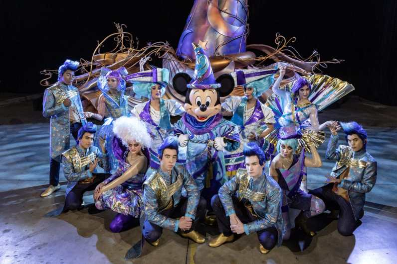 """Pictured during a backstage rehearsal of the """"Magic Happens"""" parade set to debut at Disneyland Park in California Feb. 28, 2020, Mickey Mouse, in an all-new sorcerer-inspired costume, will lead the way from atop a 15-foot tall iridescent magical hat. Performers, known as """"magic makers,"""" represent stylized aspects of """"Disney magic"""" – from beauty to strength and everything in between. The parade will come to life with an energetic musical score and new songs and will feature stunning floats, beautiful costumes and beloved Disney characters. (Joshua Sudock/Disneyland Resort)"""