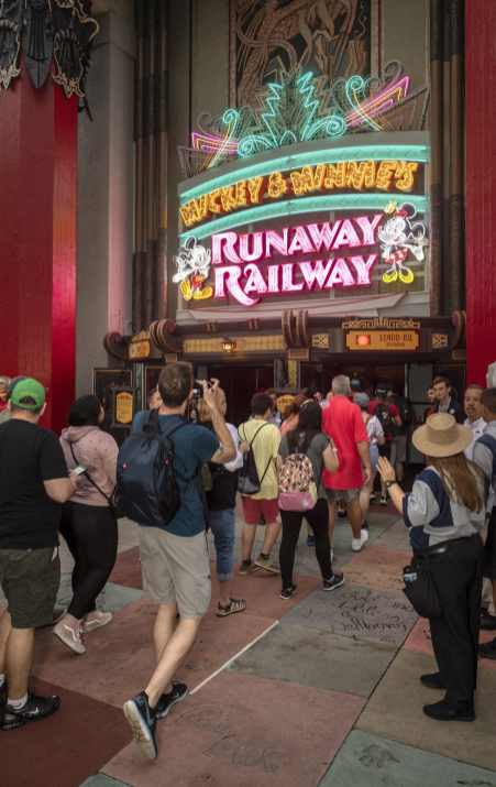 Guests walk beneath the marquee for Mickey & Minnie's Runaway Railway as they enter the new attraction on its opening day, March 4, 2020, in Disney's Hollywood Studios at Walt Disney World Resort in Lake Buena Vista, Fla. (Kent Phillips, photographer)