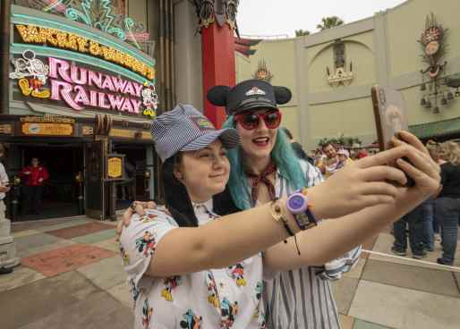 Guests stop for a selfie in front of the marquee for Mickey & Minnie's Runaway Railway on opening day of the new family-friendly attraction, March 4, 2020, in Disney's Hollywood Studios at Walt Disney World Resort in Lake Buena Vista, Fla. (Kent Phillips, photographer)