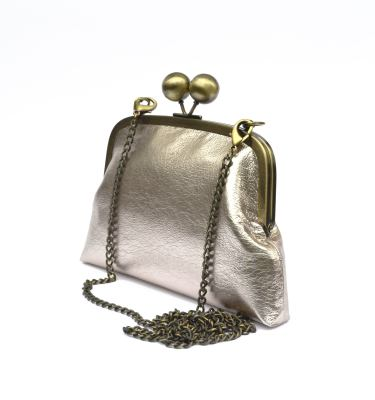 Sideview of blush champagne clutch purse with chain strap