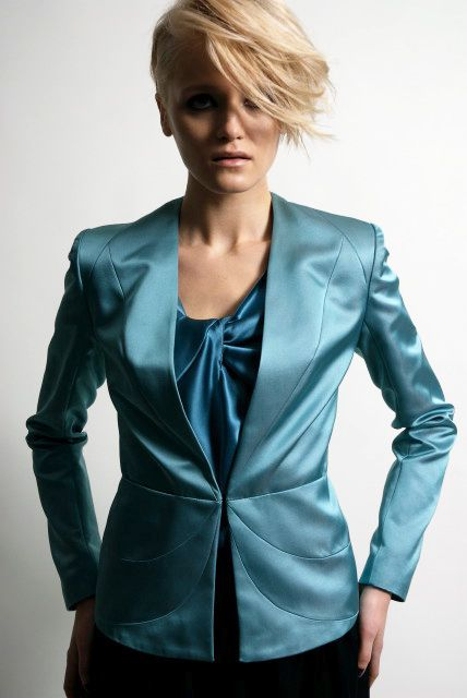 Model wearing turquoise trouser suit with turquoise silk blouse