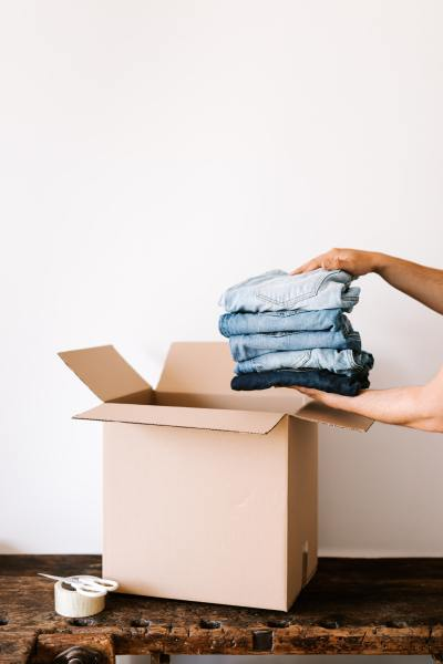 Stack of jeans being put into a cardboard box
