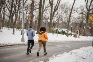 unrecognizable joggers running on roadway in winter suburb