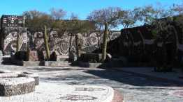 Amaicho del Valle, Museo Pachamama: stone yard with two of the creatively decorated buildings