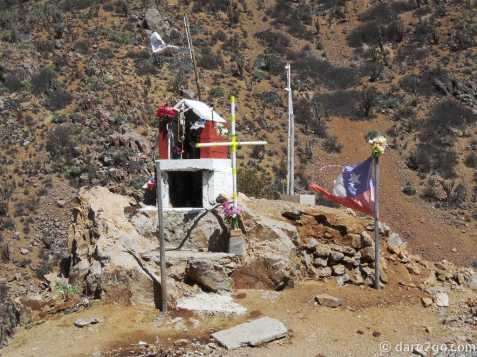 on the way to Los Pozos, Chile: roadside shrine with flags