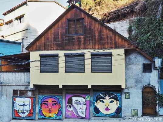StreetArt in Valparaiso, Calle Ecuador (upper section): 4 garage doors with 4 faces (on a rather plain house)