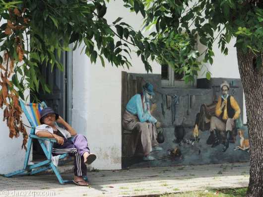Mural depicting old battlers sitting around a fire (the one on the left is 'real')