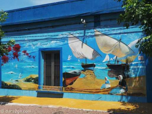 Mural showing old sailing boats and women on the beach, also on the main square of Villa 25 de Agosto