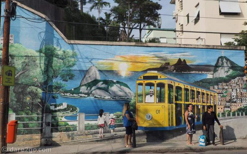 This is so Rio de Janeiro: the bright yellow Santa Teresa tram on a garden wall with people waiting for the next tram to arrive.