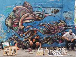 Street vendors display their wares in front of a wall covered in street art.
