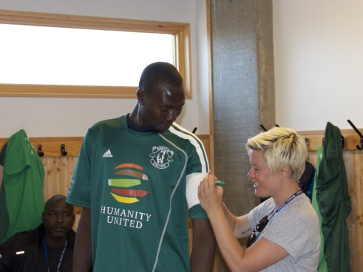 DU Coach Ambassador Margo Baker places the makeshift captain's badge on Khamis.