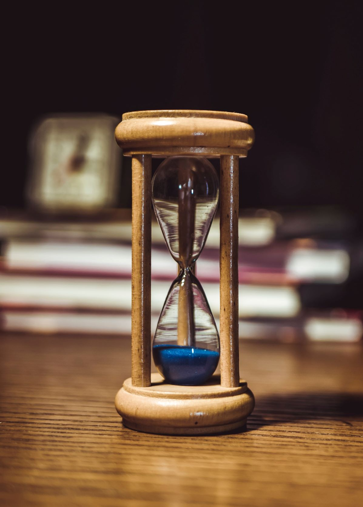 An hourglass with books and a clock in the background
