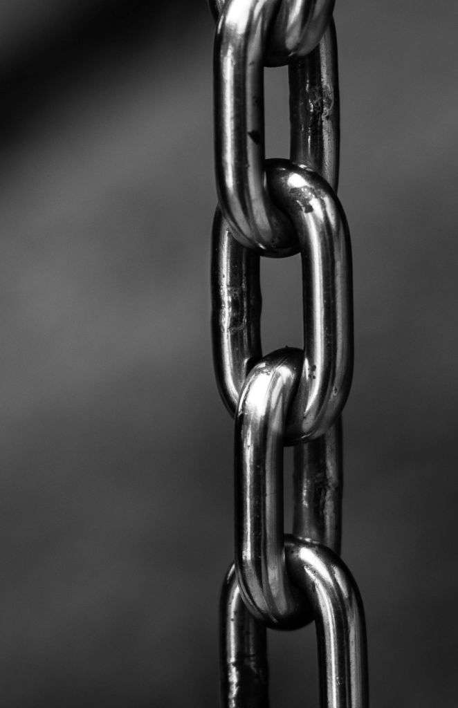 Greyscale photo of a heavy chain dangling vertically. Image credit: Pexels