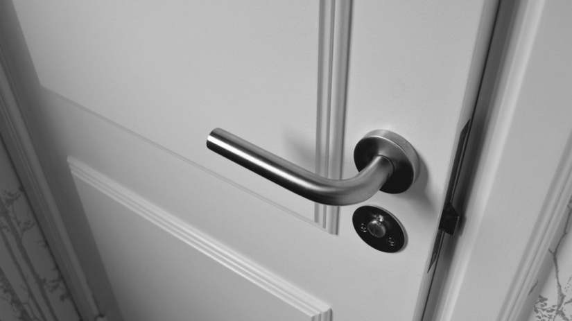 A black and white photograph of a door standing slightly open