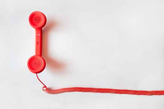 A old-style red telephone handset with cord