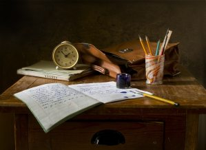 A wooden desk. Sitting on top are a copy book with a fountain pen and ink, a glass jar holding other pens and pencils, a notebook, clock and satchel.