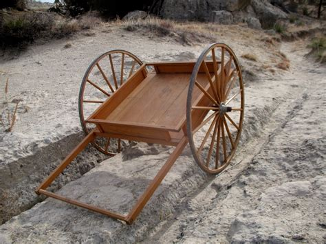 Photo of an empty wagon cart with wheels stuck in a rut