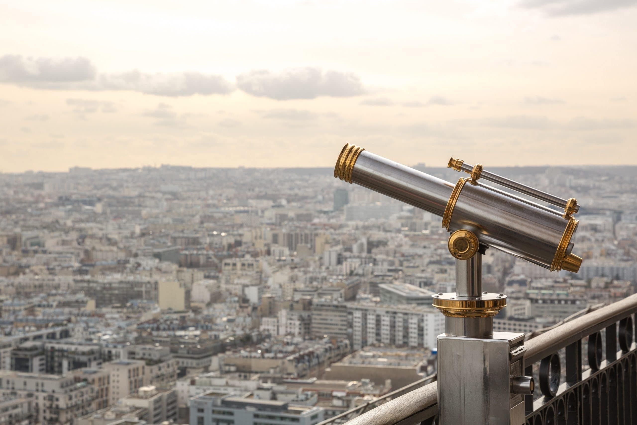 A telescope on a balcony above a cityscape