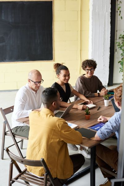 Photo of people sitting at a wooden table
