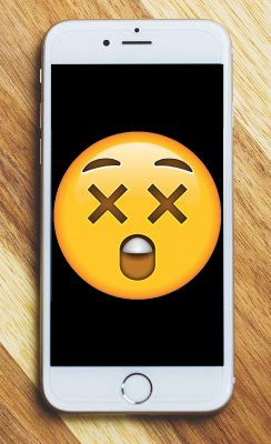 A mobile phone with a shocked/surprised emoji on the screen