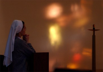 A Sister reflects and prays inside the main chapel at the Immaculata Convent in Norfolk on Feb. 7, 2003.