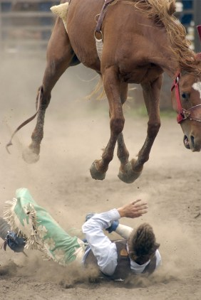 Stetson Feller of Johnston hits the dirt as his mount jumps over him during the bareback competition at the Northeast Nebraska High School Rodeo Saturday afternoon, May 31, 2003.
