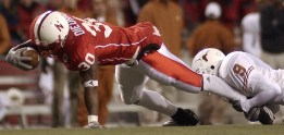 Dahrran Diedrick of Nebraska stretches out to get extra yardage as he is dragged down by Dakarai Pearson of Texas Saturday night, Nov. 2, 2002.
