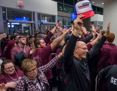 DARIN EPPERLY/DAILY NEWS LINCOLN -- Tom Schomm holds up a modified hat that reads 'Make Norfolk Great Again' while greeting Panther players after Norfolk defeated Papillion-LaVista to win the Class A championship game on Saturday night at Pinnacle Bank Arena. 3-11-17